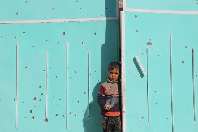 A boy stands at the gate of his house in Mosul city, Iraq, on Nov. 20, 2016. (Xinhua/Liu Wanli) (zw)