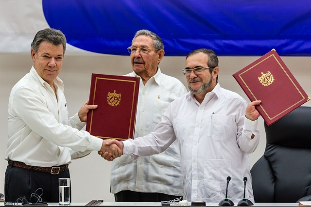 Colombian President Juan Manuel Santos (L) and Timoleon Jimenez (R), the top leader of the Revolutionary Armed Forces of Colombia (FARC), exchange pacts while Cuban President Raul Castro witnesses in Havana, capital of Cuba, June 23, 2016. (Xinhua/Liu Bin) (zw)