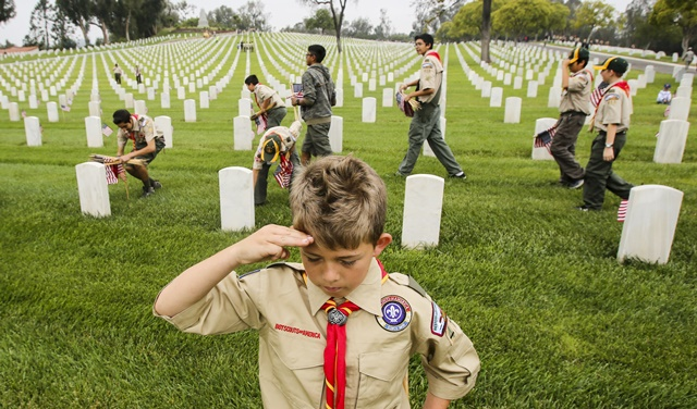 A boy scout salutes after placing U.S. flag in front of a grave stone at the Los Angeles National Cemetery, for the Memorial Day in Los Angeles, California, the United States, May 28, 2016. (Xinhua/Zhao Hanrong) (zw)