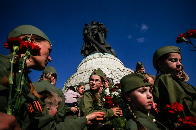People wearing Soviet army uniforms and holding flowers gather in front of a Soviet soldier statue at the Soviet Memorial in Treptower Park in Berlin, Germany, on May 9, 2016. (Xinhua/Zhang Fan) (zw)