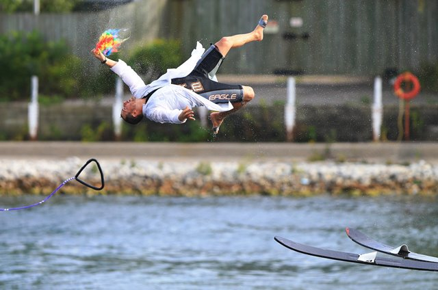 A man catches his wig as he falls into water when performing water skiing during the 2016 Canadian National Exhibition in Toronto, Canada, Aug. 24, 2016. (Xinhua/Zou Zheng) (zw)