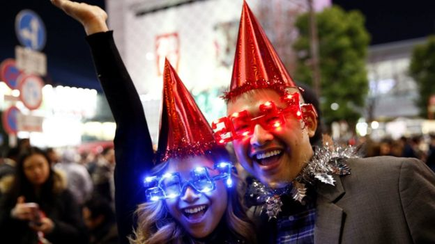 Revellers wearing glasses in the shape of 2017 pose during a new year countdown event at Shibuya crossing in Tokyo, Japan, December 31, 2016