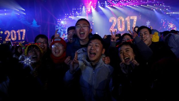 People pose for pictures as they attend a New Year