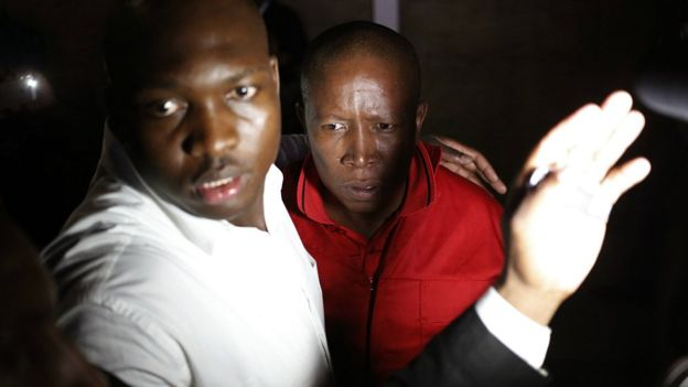 EFF leader Julius Malema, in red, is guarded after he was removed from parliament in Cape Town, South Africa, Thursday, Feb 9, 2017