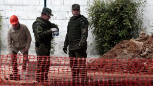 Military officers of the Hellenic Army's Explosives Ordnance Disposal stand over a hole in the ground where a World War II bomb was found during excavation works at a gas station on Sunday. (Alexandros Avramidis/Reuters)