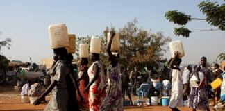 FILE (Xinhua) -- South Sudanese women carry water in a UN camp in Juba, capital of South Sudan, Dec. 22, 2013.