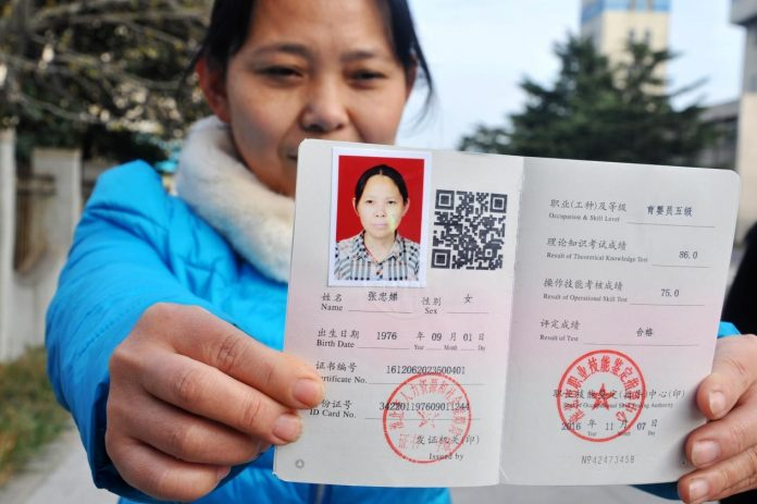 The government has launched skill training to reallocate workers laid off as a result of the effort to addressing overcapacity. Photo shows Zhang Zhongdi, a laid-off worker from Huaibei Mining Group in east China's Anhui province, is demonstrating her domestic helper certificate. (Photo by Wang Daoyu from People's Daily)
