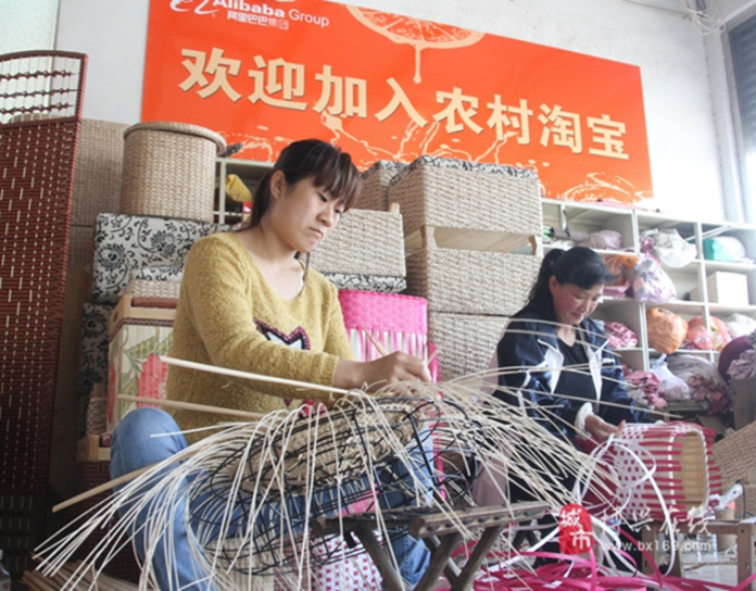 Villagers of Wantou Village, Boxing county in east China's Shandong Province make crafts. The banner on the wall reads