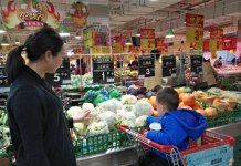 Photo taken on March 11, 2017 shows a customer buying vegetables in a Beijing-located supermarket. (Photo by Zhang Mengxu from People's Daily)