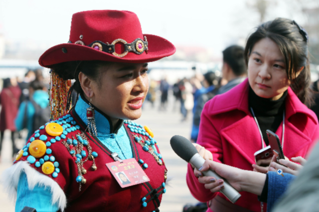 An ethnic minority delegate gives an interview outside the Great Hall of the People in Beijing. The fifth session of the 12th National Committee of the Chinese People's Political Consultative Conference kicked off on March 3, 2017. (Photo by Zhang Xiuke from People's Daily)