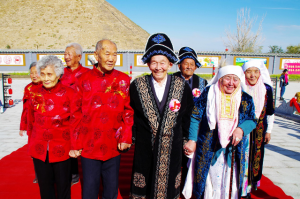 """Photo taken on October 9, 2016 shows a """"golden anniversary"""" celebration held in Barkol county of Xinjiang Uygur Autonomous Region to mark the Double Ninth Festival, a traditional Chinese festival to pay respect to the seniors. A total of 12 pairs of couples from Han and Kazak ethnic groups celebrate the day in romantic atmosphere. (Photo by People's Daily)"""