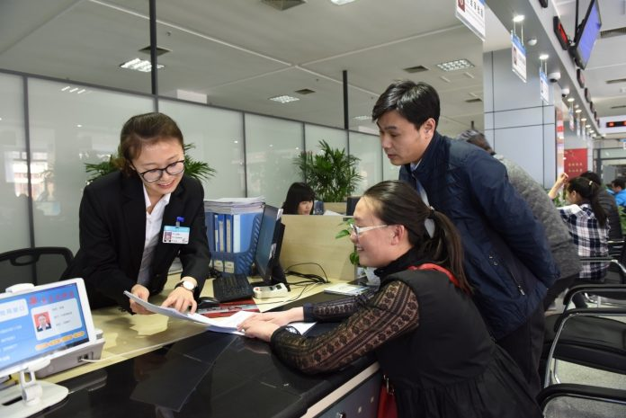 A staff with Langfang Economic & Technical Development Zone in China's Hebei province issues operation certificates for a company in the zone. (Photo by Gao Zhenyong from People's Daily)