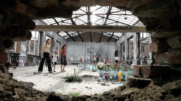 People walk 29 August 2005 in the school sports hall in Beslan that was destroyed 03 September 2004 during a hostage-taking