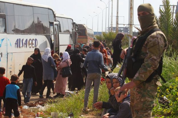 A rebel fighter stands near buses carrying people that were evacuated from the two villages of Kefraya and Foah, 15 April