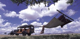 A tourist relaxes at Cottar 1920s Camp; travel insurances assures you security over the unseen