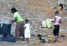 A mother cooks for her children near the sprawling Achimota dump site in the outskirts of Accra, capital of Ghana, May 30, 2012. Environmental problems is one of the big challenges that Ghana faces. The western African country recorded 14.4 percent GDP growth last year, but it has to balance the development and environment protection. (Xinhua/Mary T. Richter) (lyq)