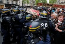 "French riot police surround demonstrators who hold a placard with the message, ""The State is not an Company"", the day after the country went to the polls, in Paris, France, May 8, 2017. REUTERS/Jean-Paul Pelissier"