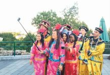 Foreigners in ancient Chinese royal dresses take selfies at Jingshan Park in Beijing. (People's Daily Overseas Editon/Gao Bing)