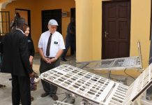 Elder and Sister Redlin (from) right with Dr. Damien Punguyire (left) Inspecting the equipment