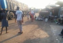 Some trader cooking close to vehicles at Yeji