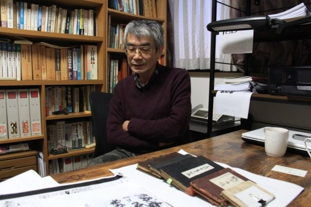Ono is introducing his research experiences. On the desk are the war diaries he collected from invading Japanese soldiers. Photo by Liu Junguo from People's Daily