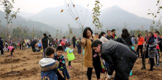 Children and parents join a tree-planting activity held at Qinling National Botanical Garden, northwestern China's Shaanxi province on Mar. 10, 2018. (Photo by CFP)