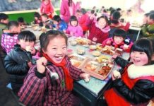 Left-behind children, whose parents have left rural areas to become migrant workers in towns or cities, enjoy their free lunch in the school canteen in central China's Anhui province. (Photo from People's Daily Online)