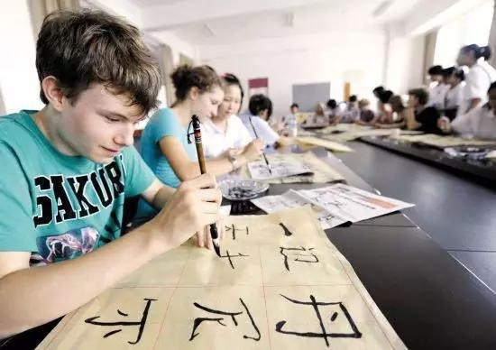 A Russian student writes Chinese characters with Chinese calligraphy brush. (Photo from People's Daily Online)