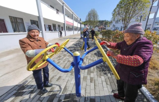 Senior citizens do physical exercises at a new eldercare service center in a village of Guangchang county, Jiangxi province, Jan. 11, 2018. (Photo by Zeng Henggui from CFP)