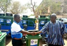 Mr John Sackey (left) handing over waste bins and motorized tricycles to Mr Joseph Amiyure MCE for Bolga