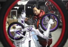 A worker is assembling a bike at a factory based in Quzhou county, north China's Hebei province on Jan. 24, 2018. A total of 15 enterprises in the county have been granted the right to self-manage imports and exports. Their products have been sold to Africa, Southeast Asia and Europe. (Photo by Hu Gaolei from CFP)