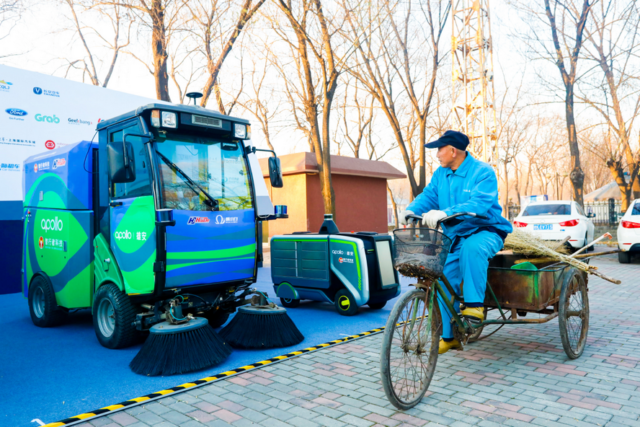 Photo taken on December 20, 2017 shows a sanitation worker and a driverless street sweeper in the Xiongan New Area, north China's Hebei province. (Photo by Yan Yuxiao from People's Daily online)