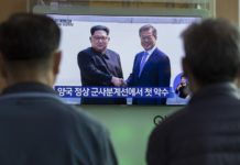 People watch news from a screen on the meeting of South Korean President Moon Jae-in and top leader of the Democratic People's Republic of Korea (DPRK) Kim Jong Un, at a railway station in Seoul, South Korea, April 27, 2018. (Xinhua/Lee Sang-ho)