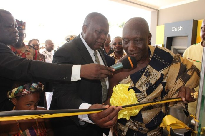 Mr Robert Adamu, Head of Support Services Department of GCB assisting the Paramount Chief of Tefle Traditional Area to commission the Sogakope branch of the Bank.