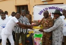 Photo showing members of the NGO (left) presenting the items to Prison officials (right) as other members and prison officials look on