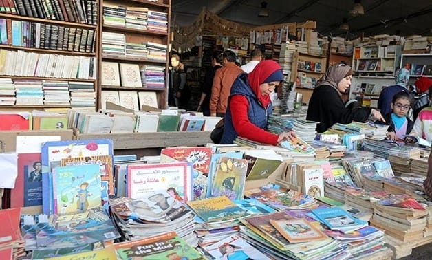 People browse through books on a stand at the Cairo International Book Fair, in Cairo - Reuters