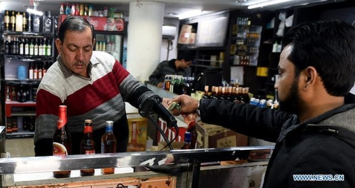 A man buys liquor at a shop in New Delhi, India, on Feb. 10, 2019. As death toll mounted in two northern Indian states of Uttar Pradesh and Uttarakhand, police have launched a massive crackdown on the illegal dens of spurious liquor manufacturing places, officials said Sunday. Over 200 people have been detained and cases registered against the persons for manufacturing and selling liquor without authorization. Officials confirmed the death toll has mounted to 72, however, local media reports suggested the tragedy has claimed over 100 lives. (Xinhua/Zhang Naijie)