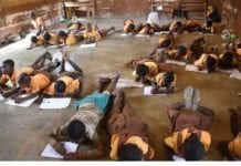 School children lie on floor to write examination
