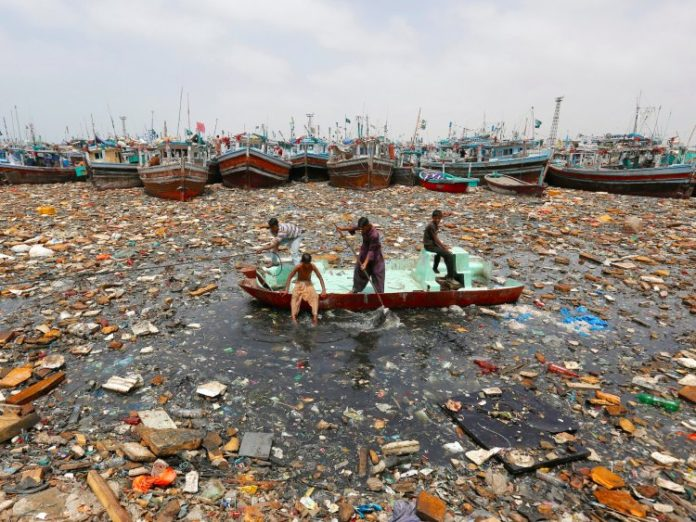 Boys aboard an abandoned boat collect recyclable items through polluted waters in front of fishing boats at Fish Harbor in Karachi, Pakistan, August 17, 2016. Reuters