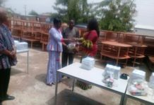 Madam Paulina Patience Abayage, the Upper East Regional Minister presenting the items to Madam Elizabeth Asigri, the Deputy Director of Education