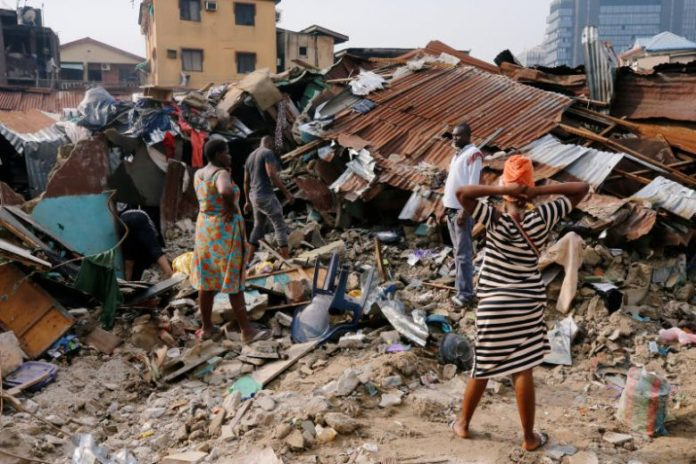 A woman searches for belongings at the site of a collapsed building in Nigeria's commercial capital of Lagos, Nigeria, on March 14, 2019.PHOTO: REUTERS