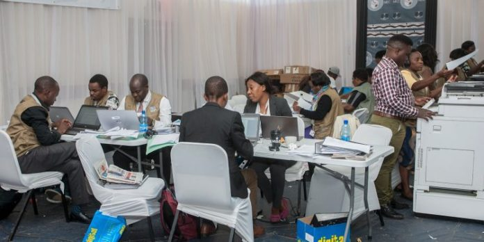 The Malawi Electoral Commission (MEC) staff members work to tabulate and tally votes heavily guarded by military personnel at the National Tally Center. Photo: AMOS GUMULIRA / AFP