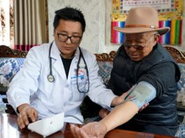 A doctor on a house call checks blood pressure and glucose for a patient in a village in Nyingchi, Tibet Autonomous Region. (By Shen Shaotie, People's Daily)