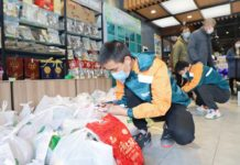 Couriers pack food ordered by customers through social platform WeChat. A Zhejiang-based agricultural company cooperates with local postal office to launch non-contact delivery on Feb. 13, 2020. The commodities all come from agricultural bases and are packed at each store of the company. They will be delivered by couriers of the postal office after orders are placed online. Photo by He Xinchao, People's Daily Online
