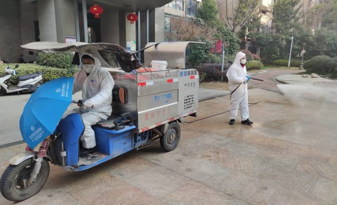 Sanitation workers disinfect in a residential community in Jianghan district, Wuhan, central China's Hubei province. (Photo by Li Changlin, People's Daily Online)