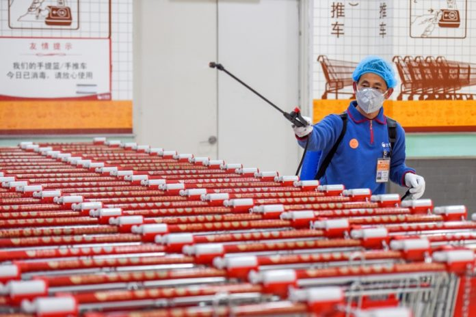 On Feb. 1, an employee disinfects the shopping carts at hypermarket RT-Mart in Jingzhou, central China's Hubei province.