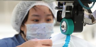 A worker makes medical protective suits at Ji Hua 3502 Career Apparel Ltd., Shijiazhuang, north China's Hebei Province, Feb. 3, 2020. (Photo by Wang Baolong from People's Daily Online)
